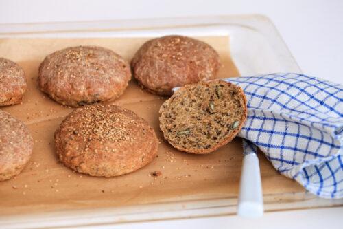 Friskbagte glutenfri burgerboller på skærebræt af lyst træ