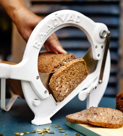 Glutenfri rugbrød skæres i skiver med hvid brødskærer